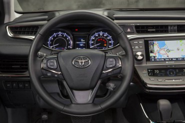 A thick, contoured leather steering wheel has very good auxiliary controls. This is a non-hybrid dash as noted by the tachometer.