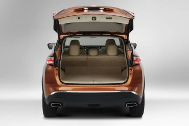 The power liftgate opens to a large cargo area with a flat deck.